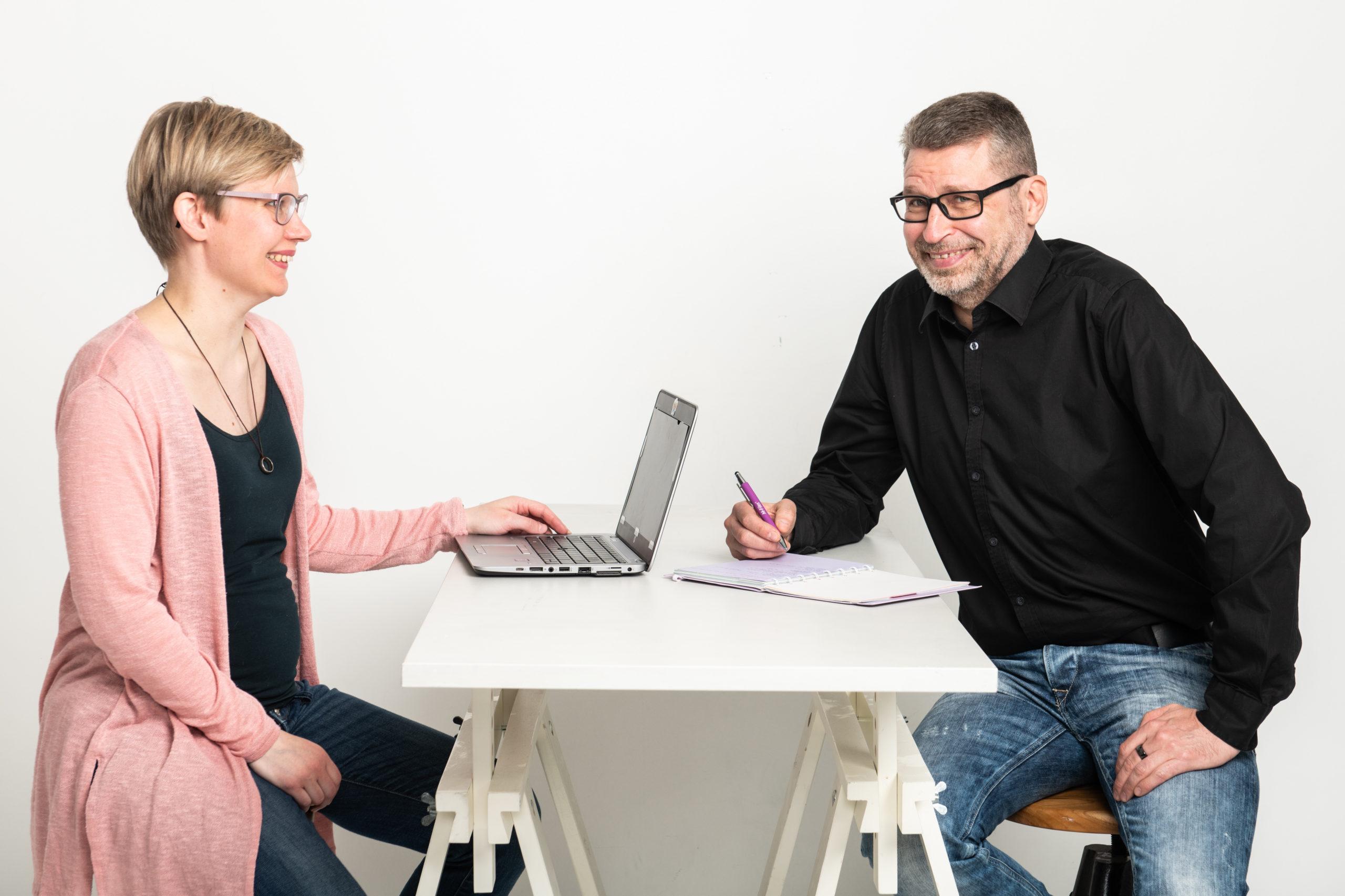 Kaksi henkilöä on neuvottelussa pöydän ääressä.