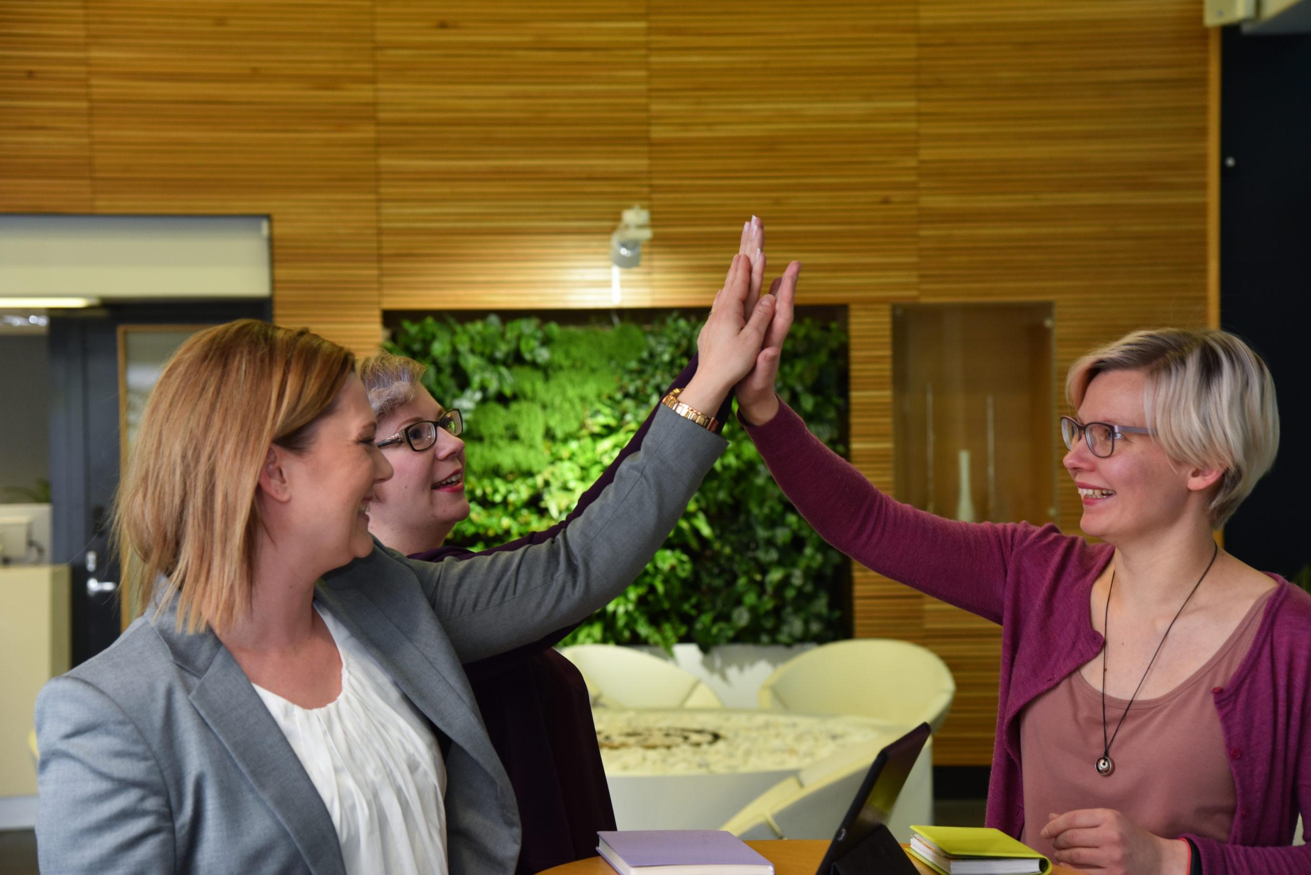 Kolme henkilöä lyö kädet yhteen, high five!