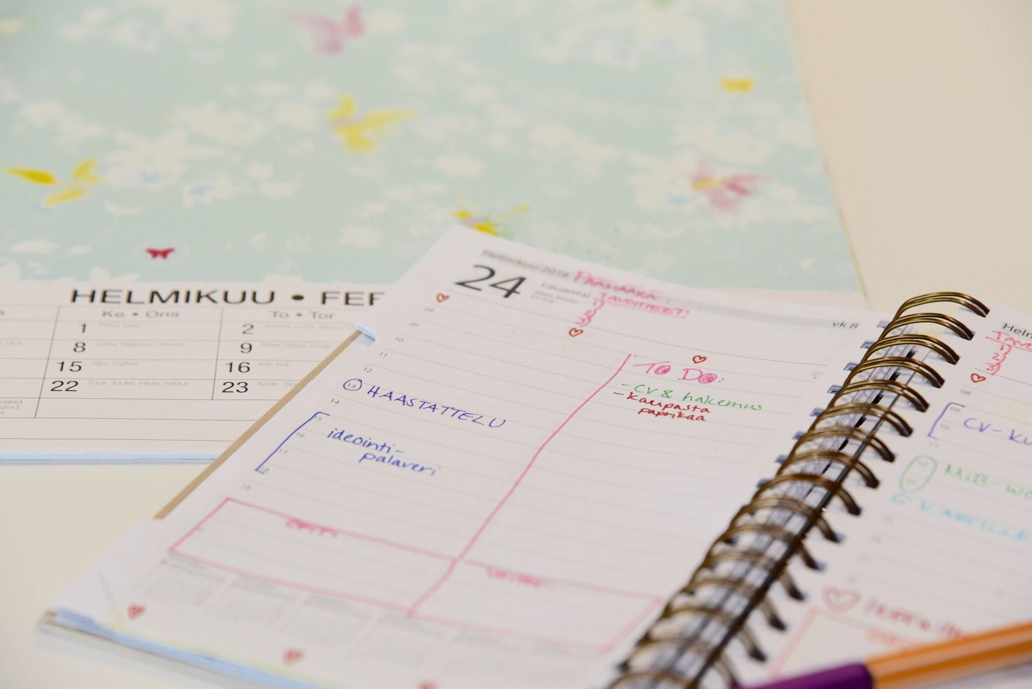 Kalenteri avoinaisena pöydällä.