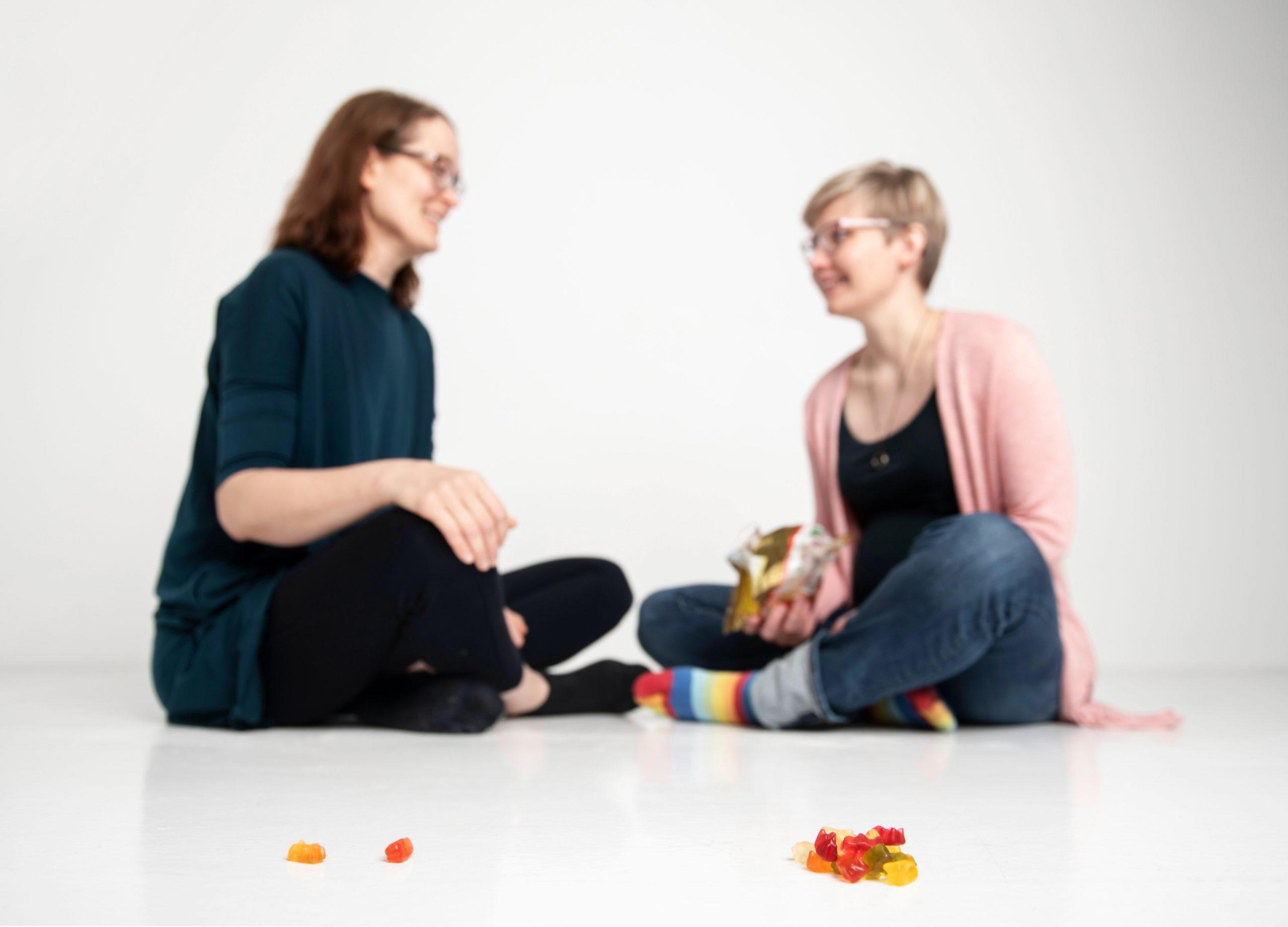 Kaksi henkilöä istumassa lattialla jakamassa nallekarkkeja. Toisella pari, toisella iso kasa.