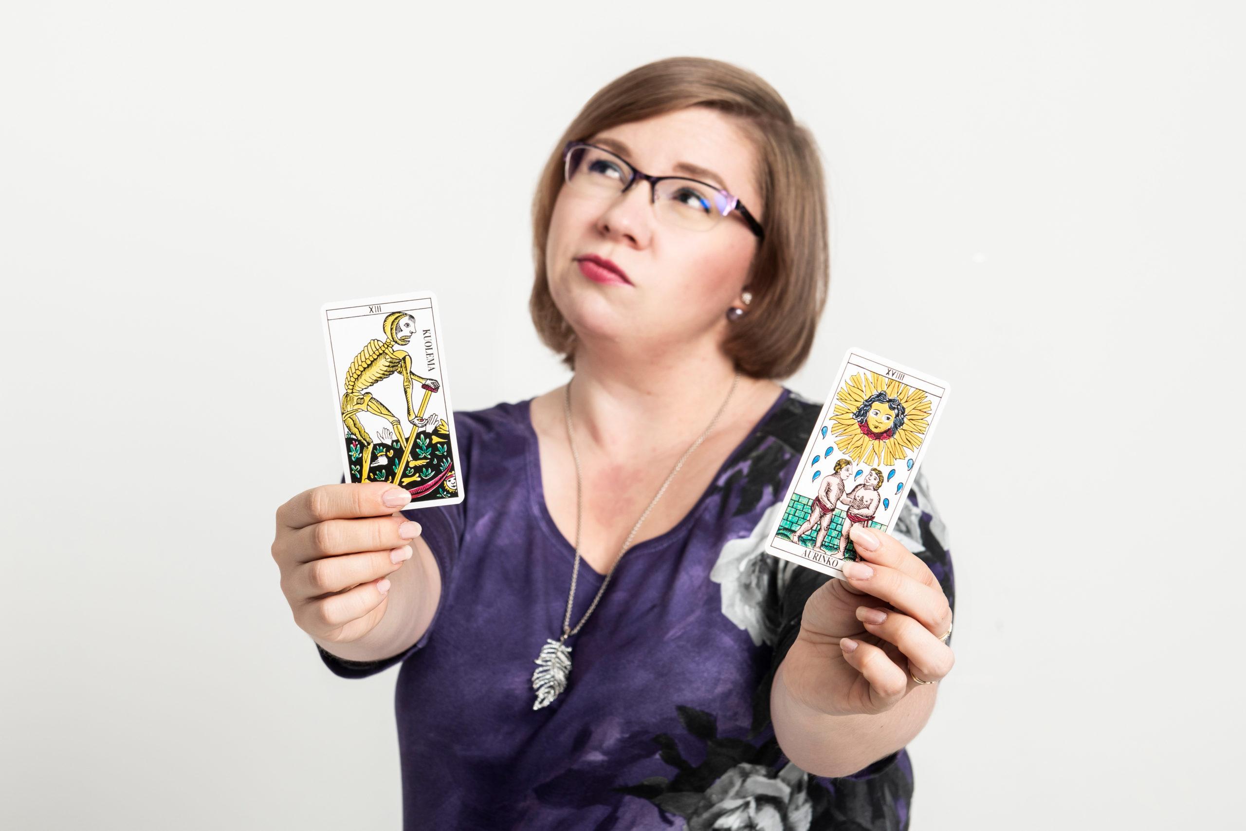 Henkilö puntaroi kahden tarotkortin välillä. Kortit ovat Kuolema ja Aurinko.