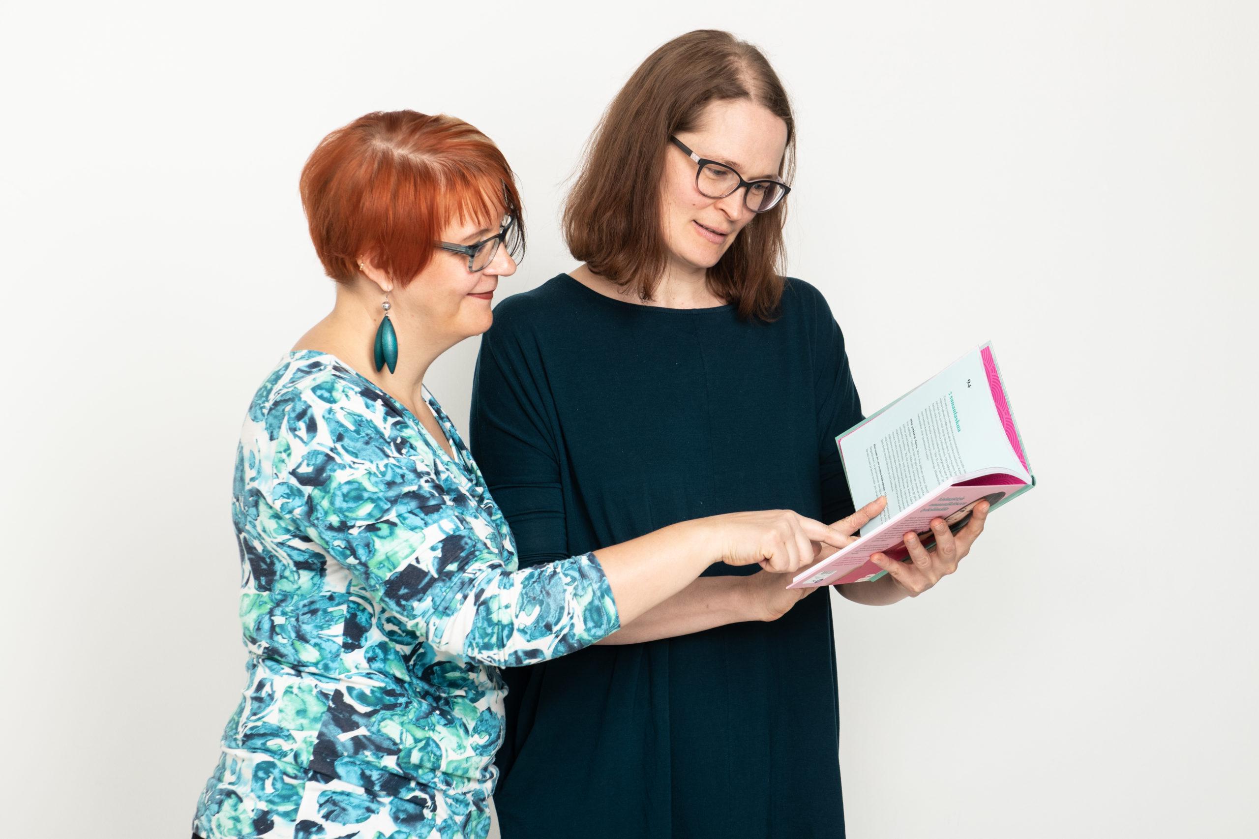 Kaksi henkilöä tutkimassa kirjaa.