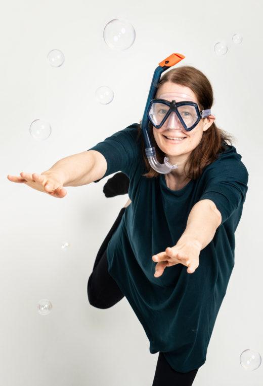 Nainen snorkkeli kasvoillaan syöksyy eteenpäin