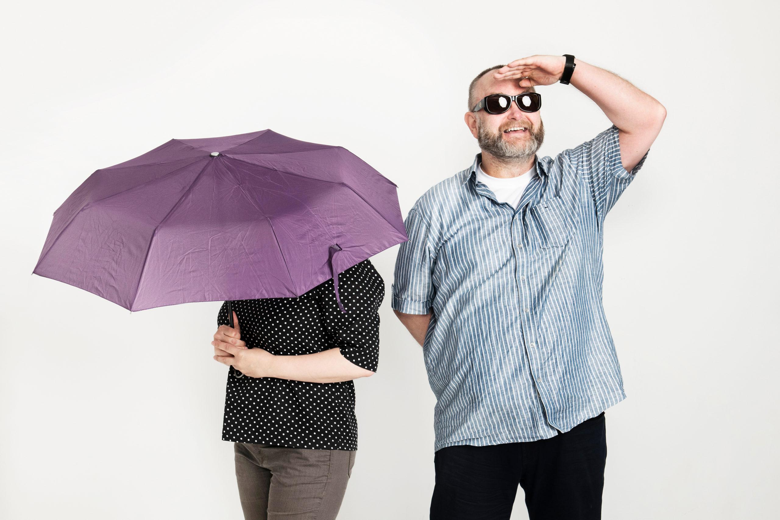 Kaksi henkilöä, toinen piiloutunut sateenvarjon alle, toinen hymyilee ja tähyilee aurinkolasit silmillä.