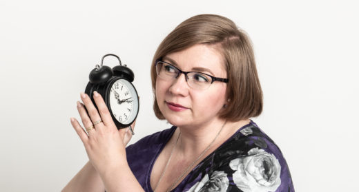 Henkilö kuuntelee kädessään olevaa herätyskelloa.
