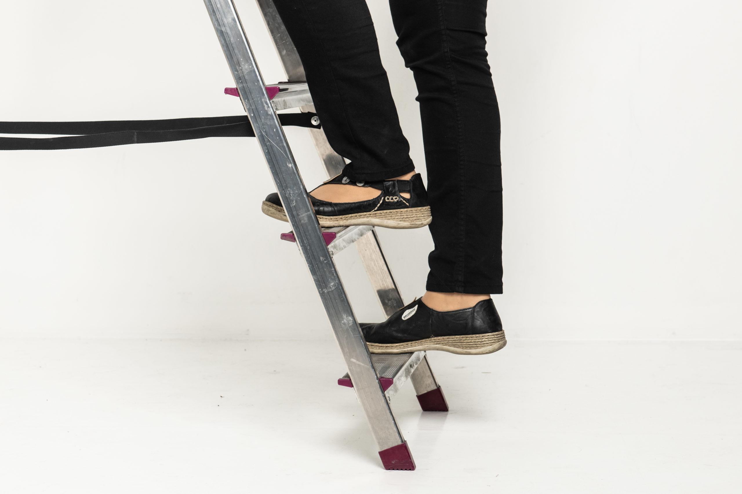Henkilö nousee tikkaita ylöspäin, vain jalat näkyvät.