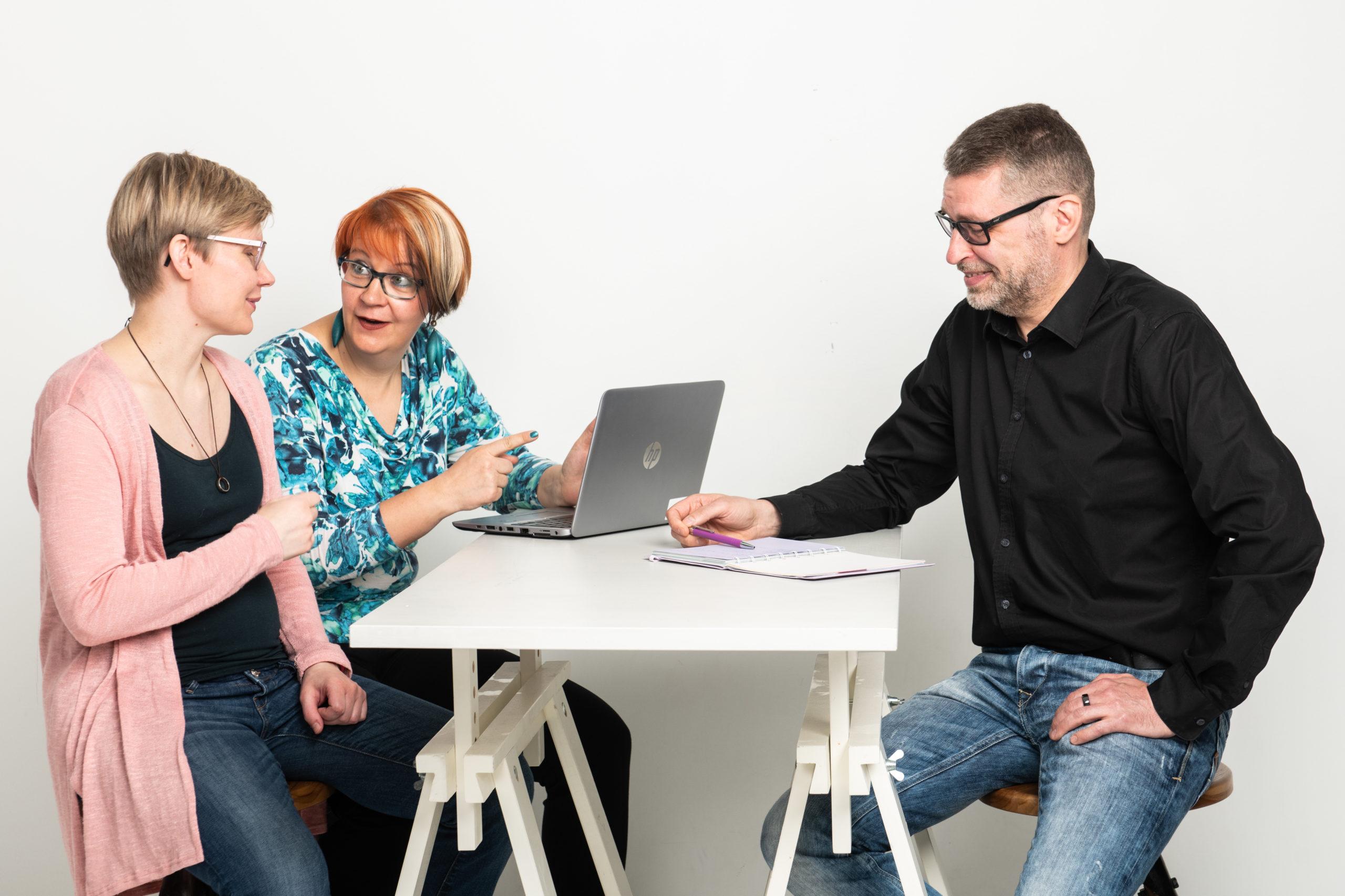 Kolme henkilöä pöydän ja läppärin ääressä.