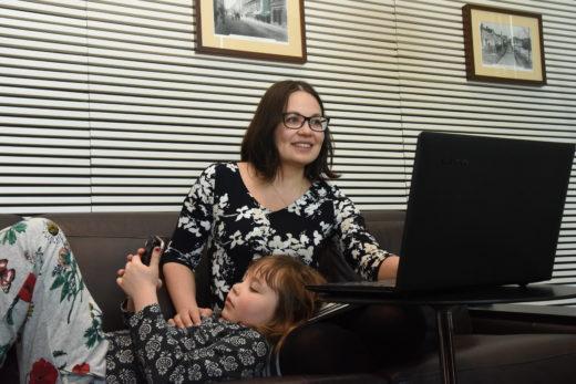 Äiti tekee töitä läppärillä, lapsi loikoilee sohvalla pää äidin sylissä ja katselee kännykkää.