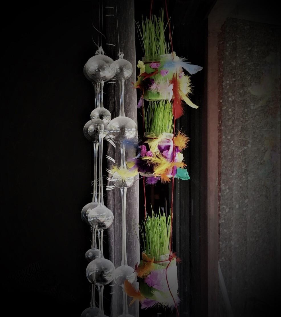 Rairuohoa höyhenillä koristellussa kolmikerroksisessa amppelissa.