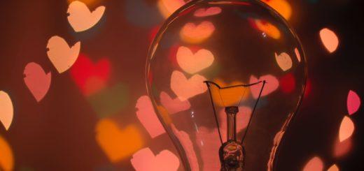 Sammunut hehkulamppu punasävyisellä tummalla taustalla. Taustassa punaisia sydänkuvioita.