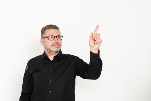 Henkilö koskettaa sormellaan saippuakuplaa.
