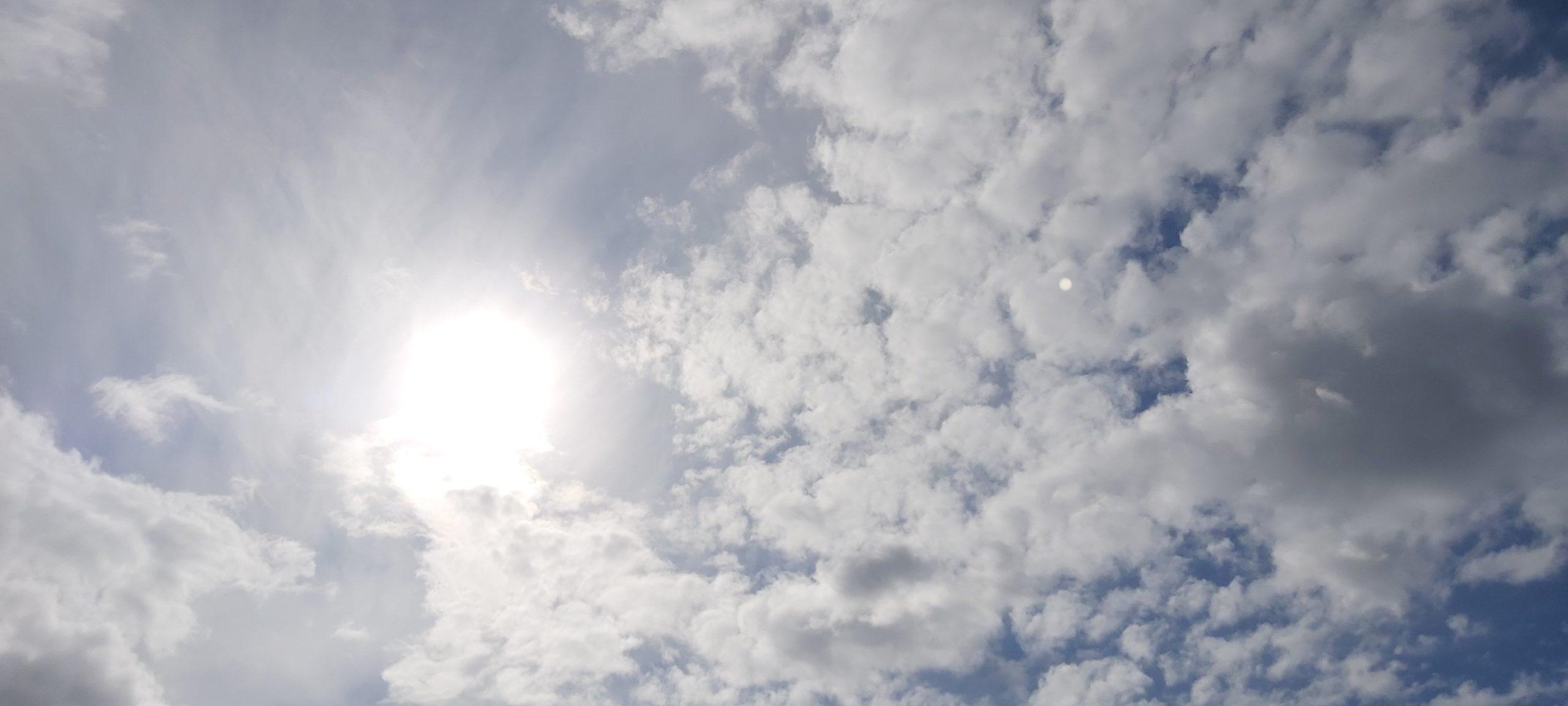 Aurinko ja vaaleita pilviä sinisellä taivaalla.