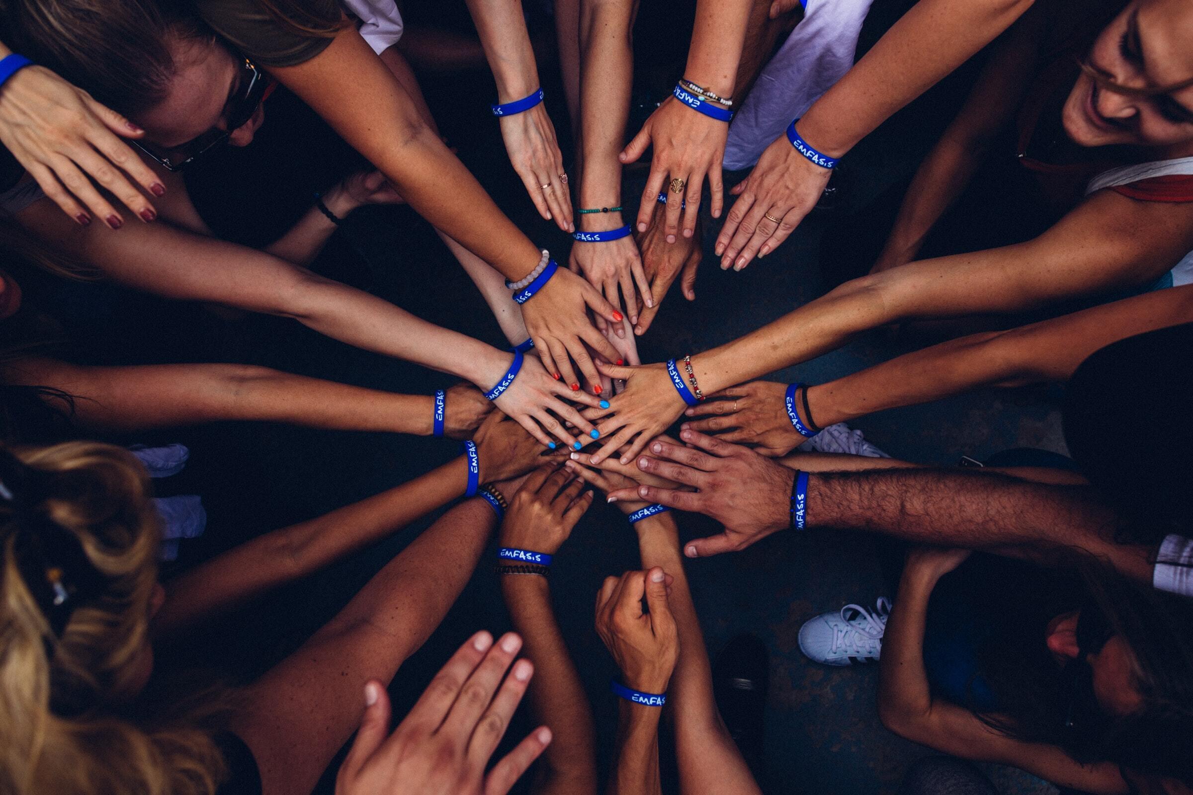 Monta kättä yhdessä piirin keskellä.