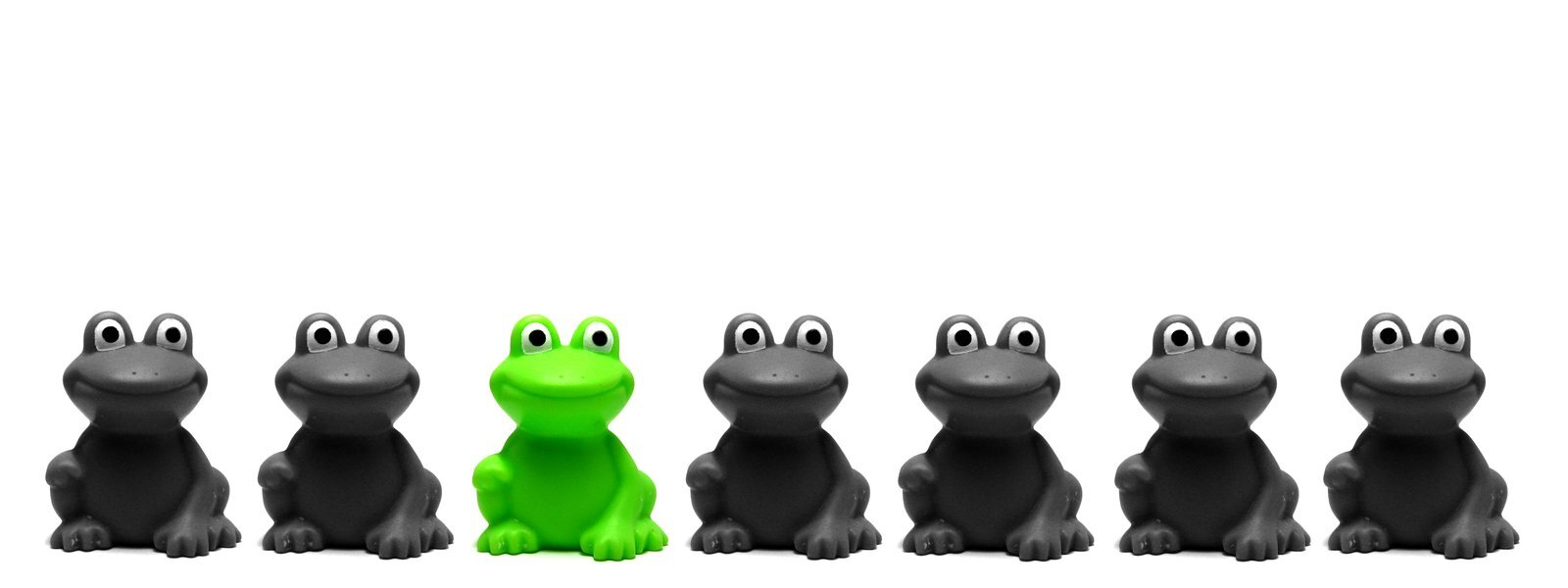 Sammakoita rivissä, yksi vihreä, muut mustia.