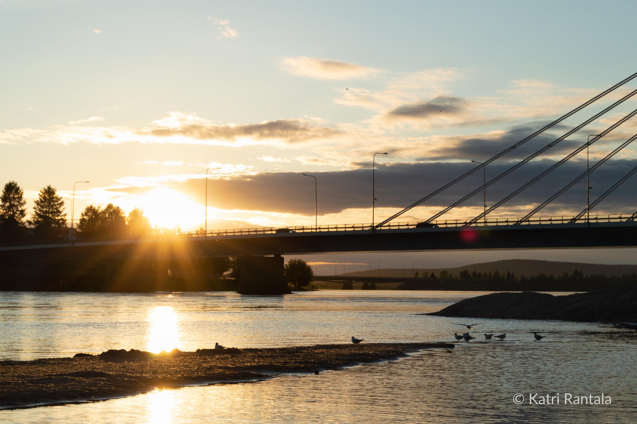 Silta joen yli, taustalla laskeva aurinko.