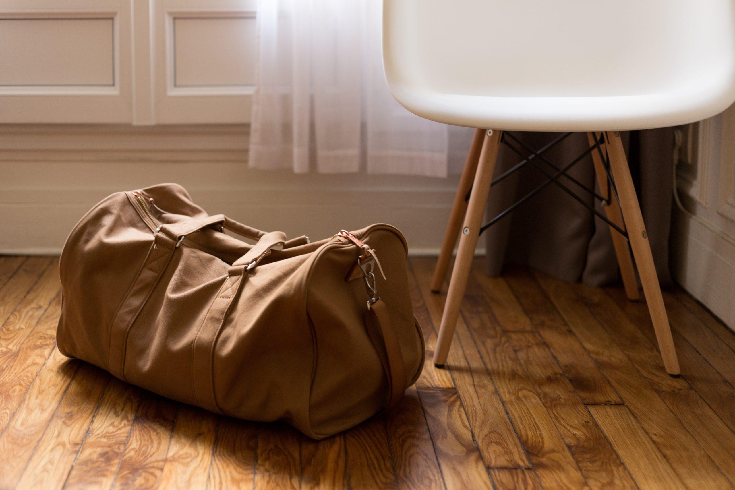 Täysi laukku lattialla tuolin vieressä.