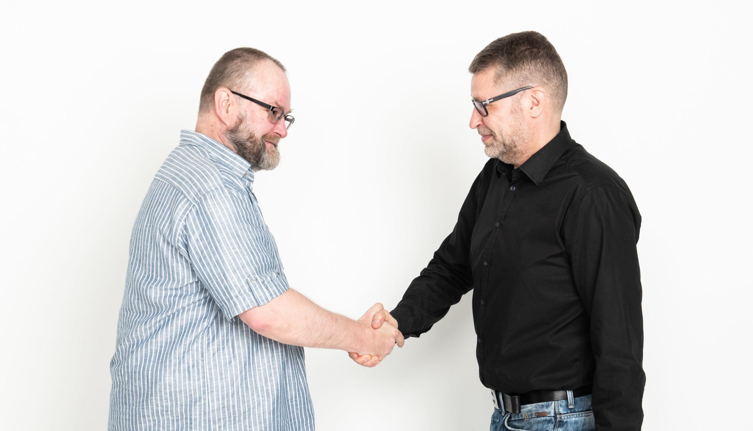 Kaksi henkilöä kättelee.