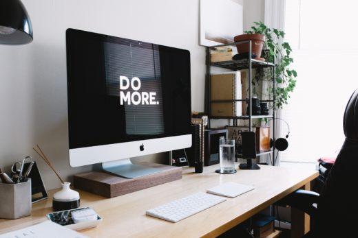 """Työpöytä, jolla iso tietokoneen näyttö, jossa lukee """"Do more""""."""