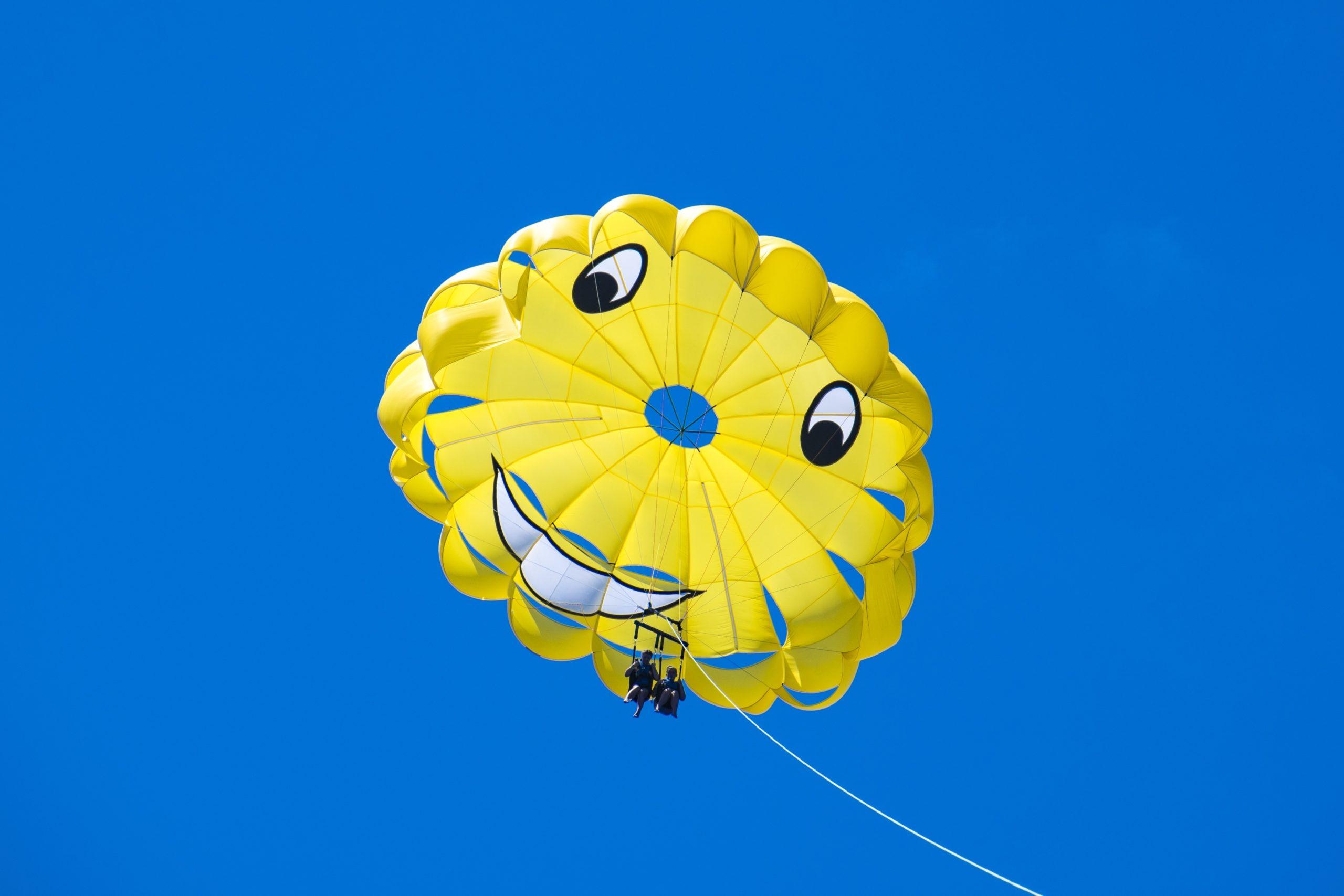 Keltainen laskuvarjo sinisellä taivaalla.