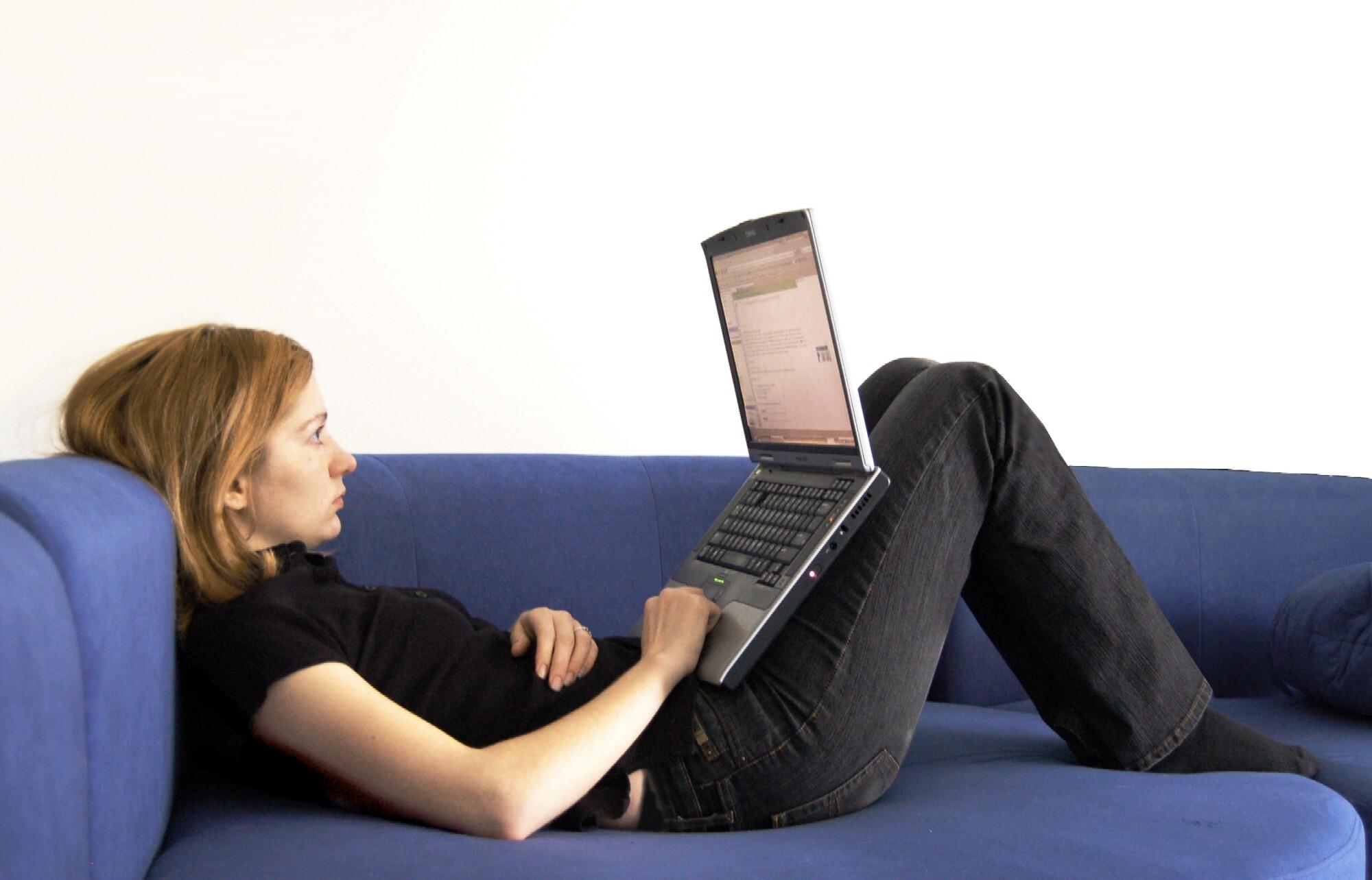 Henkilö makaa sohvalla läppärin kanssa.