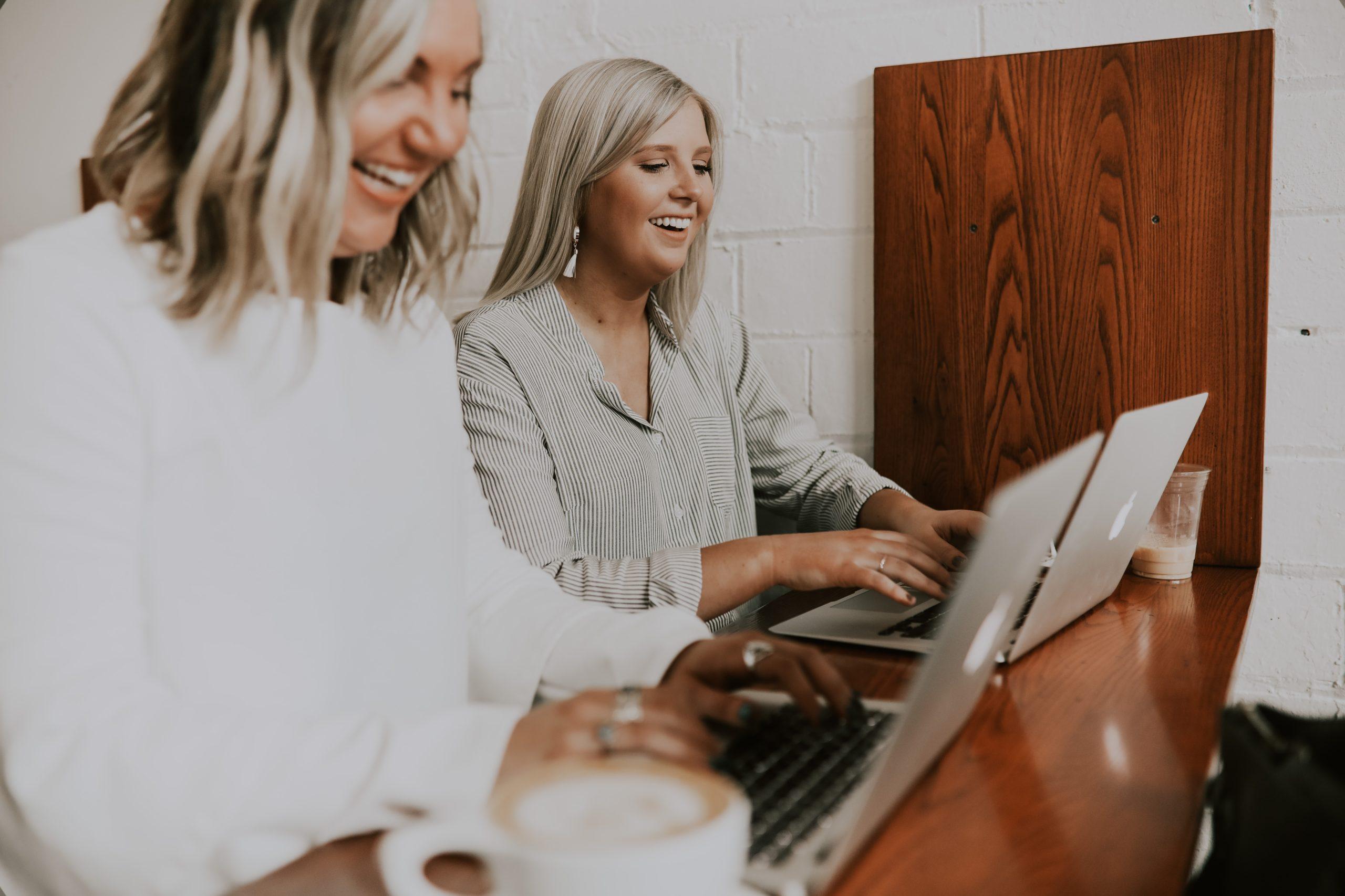 Kaksi naistaa työskentelee vierekkäin tietokoneilla nauravin kasvoin.