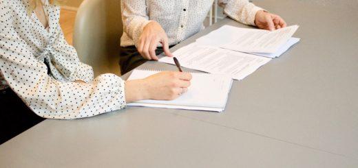Kaksi naista työskentelee papereiden ääressä, kasvot ei näy.