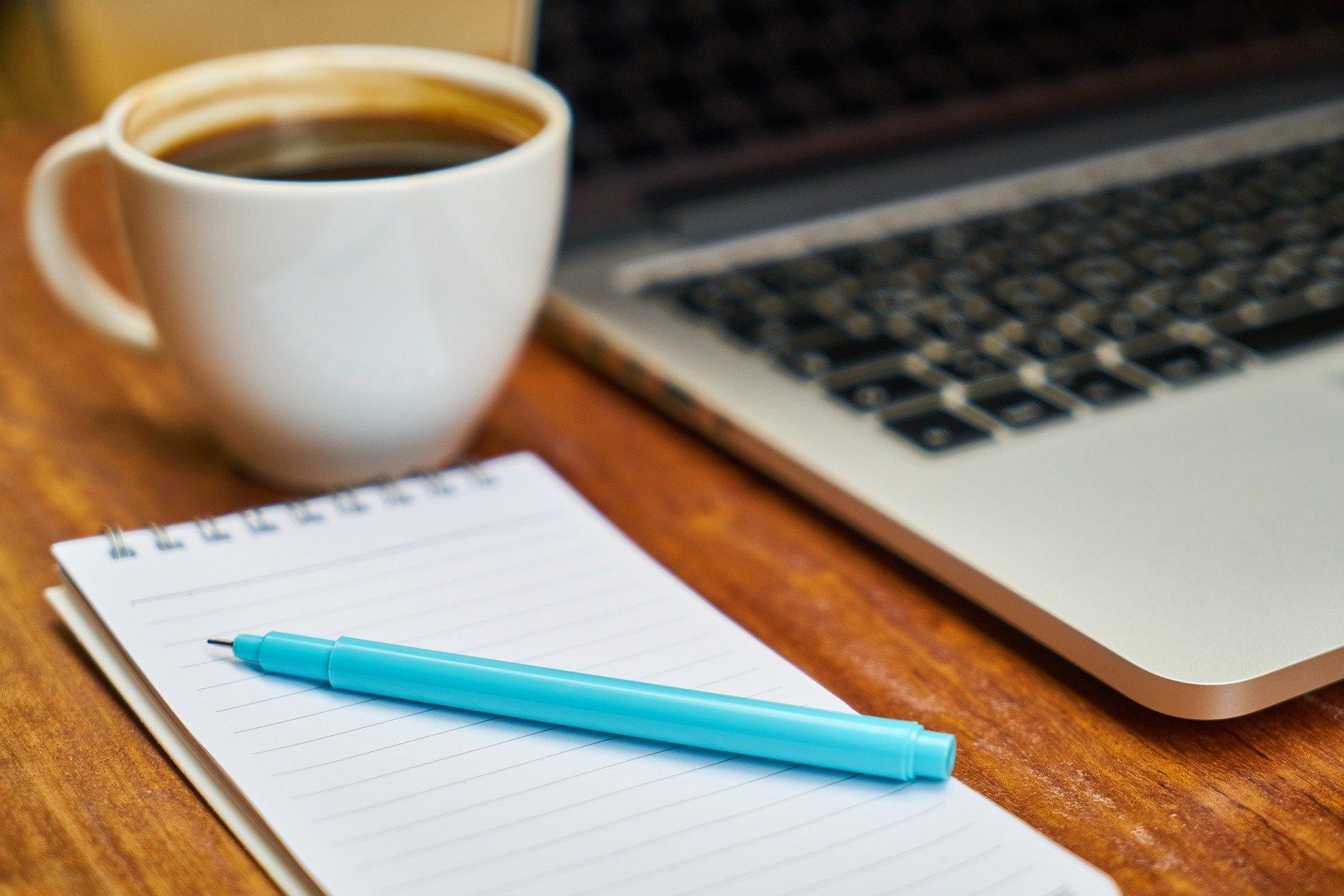 Läppäri, muistilehtiö, kynä ja kahvikuppi pöydällä