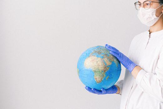 Ihminen maski kasvoillaan pitää maapalloa hanskakäsissään