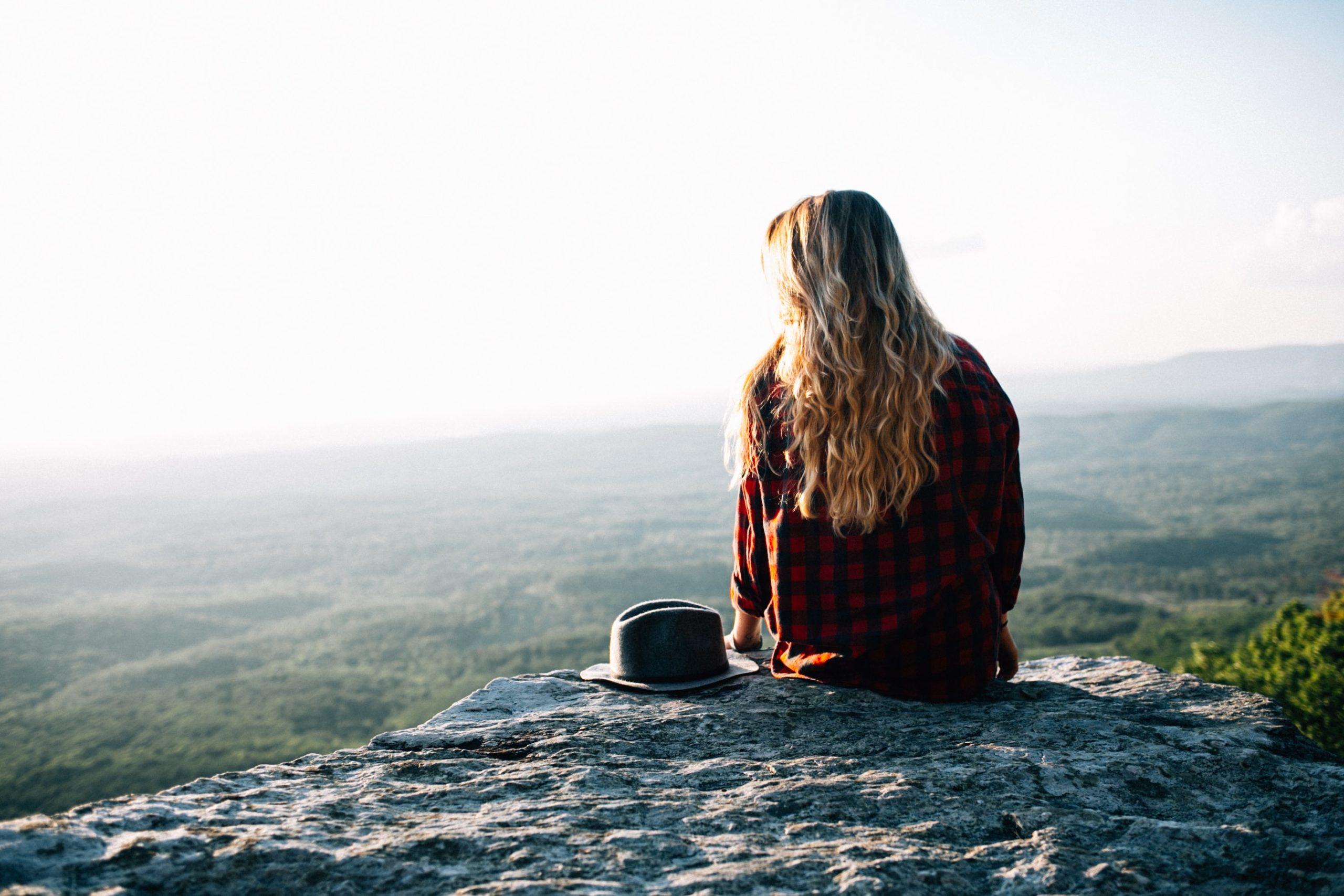 Nainen ja hattu kalliolla