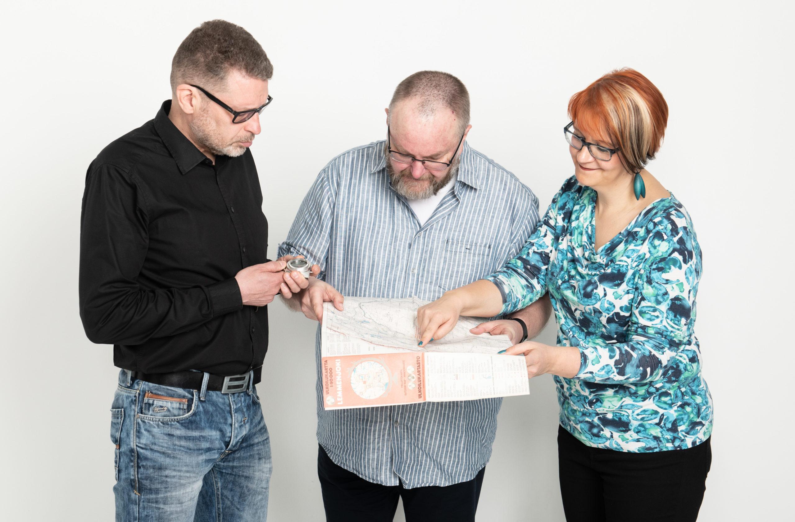 Kolme ihmistä tekee suunnitelmia ison paperin ympärillä.
