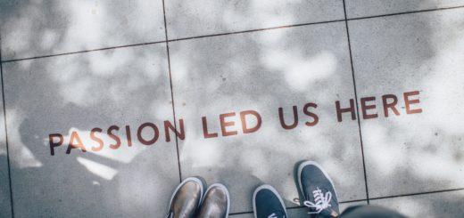 """Kaksi ihmistä seisoo jalkakäytävällä """"Passion led us here"""" -tekstin edessä"""