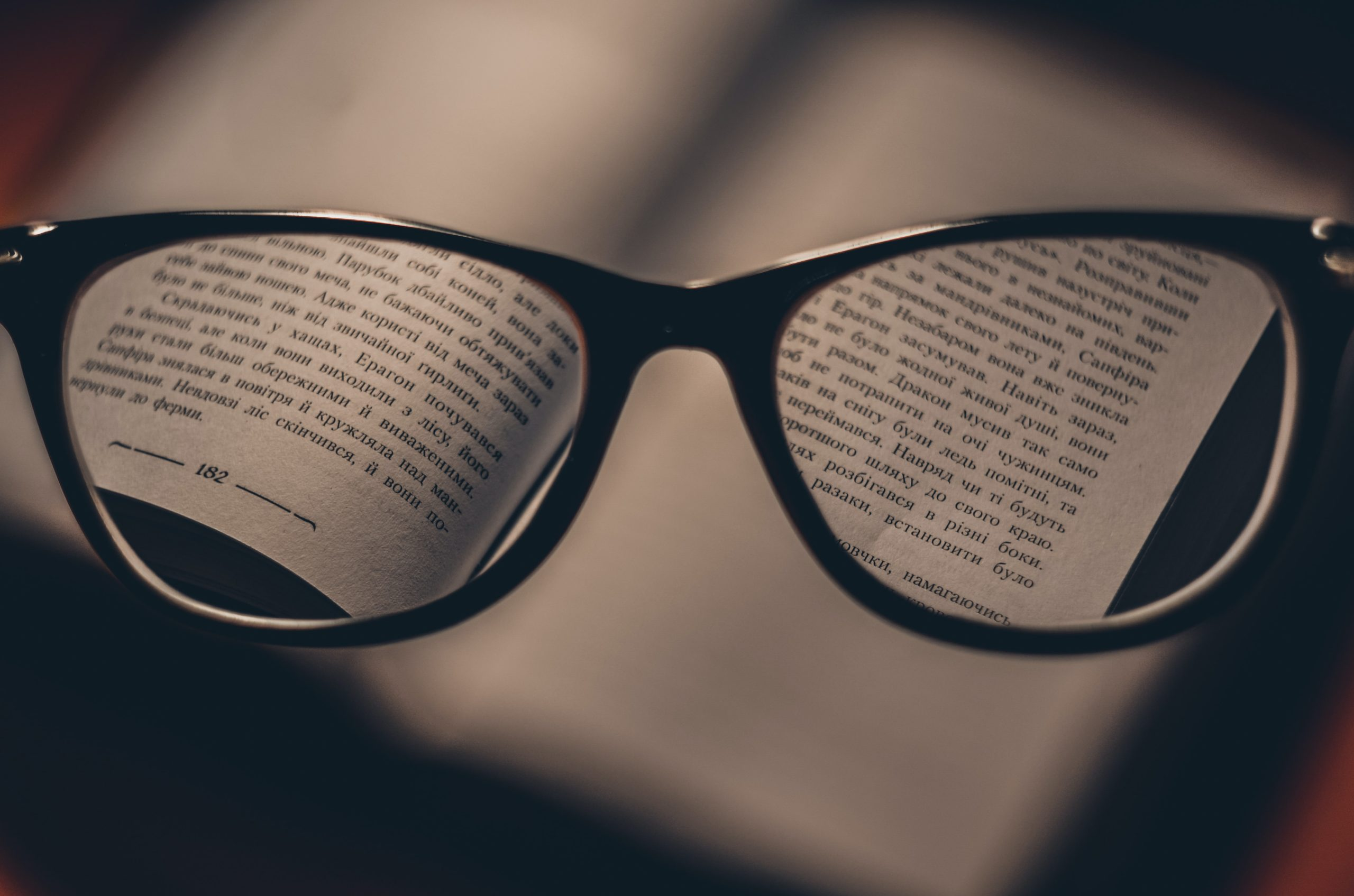 Silmälasit avoimen kirjan päällä