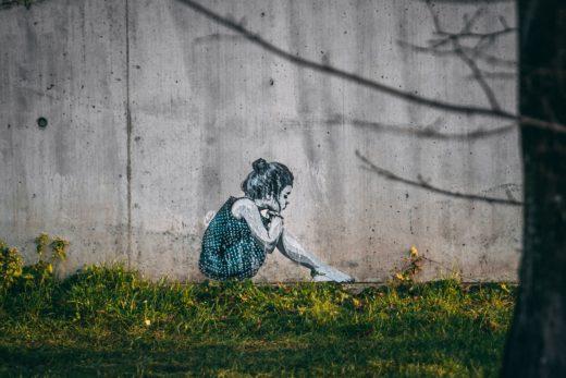 Tyttö istuu nurmikolla.